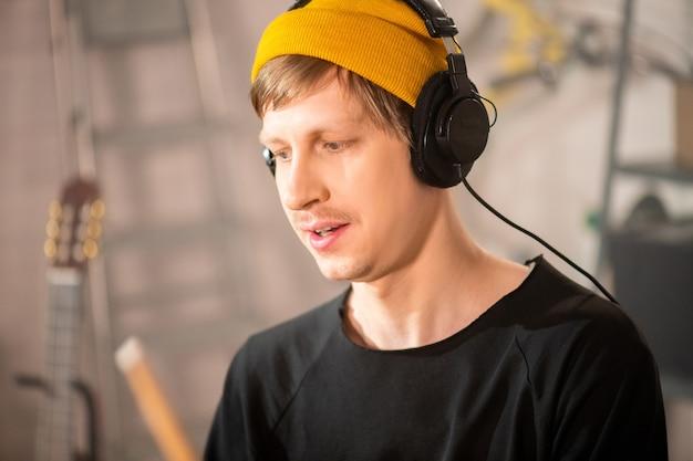 Młody perkusista w czapce i słuchawkach nagrywa nową muzykę siedząc przy zestawie perkusyjnym w garażu podczas indywidualnej próby
