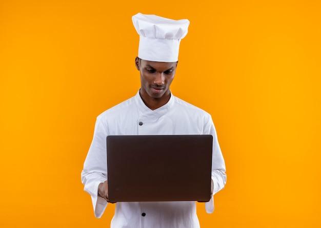 Młody pewny siebie afro-amerykański kucharz w mundurze szefa kuchni patrzy na laptopa na białym tle na pomarańczowym tle z miejsca na kopię