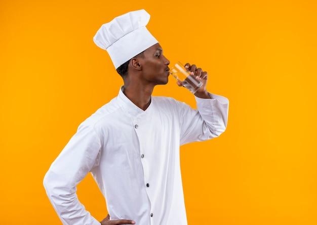 Młody pewny siebie afro-amerykański kucharz w mundurze szefa kuchni stoi bokiem i pije szklankę wody na białym tle na pomarańczowym tle z miejsca na kopię