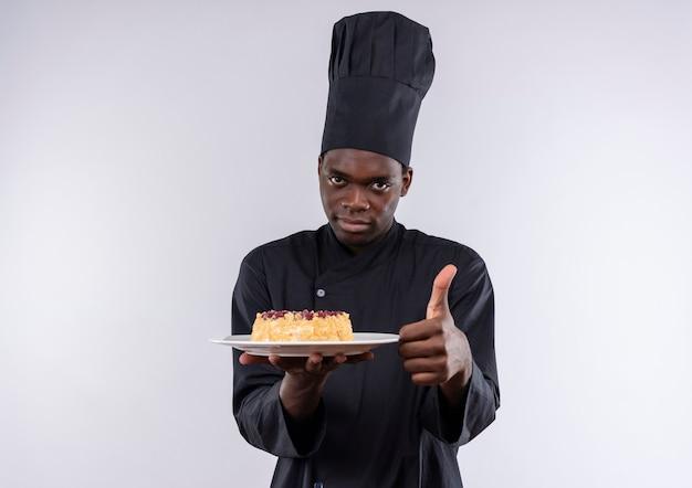 Młody pewny siebie afro-amerykański kucharz w mundurze szefa kuchni trzyma ciasto na talerzu i kciuki do góry na białym z miejsca na kopię