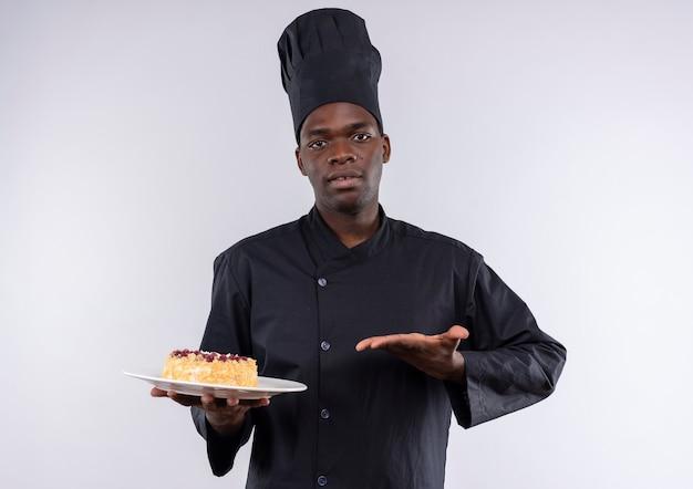 Młody pewny siebie afro-amerykański kucharz w mundurze szefa kuchni trzyma i wskazuje ciasto na talerzu na białym tle z miejsca na kopię