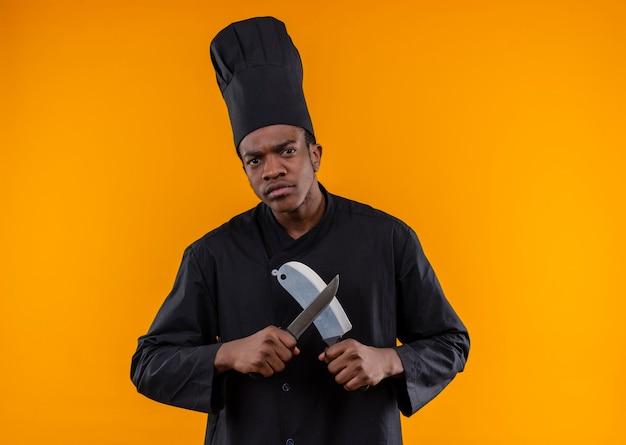 Młody pewny siebie afro-amerykański kucharz w mundurze szefa kuchni trzyma noże na białym tle na pomarańczowym tle z miejsca na kopię