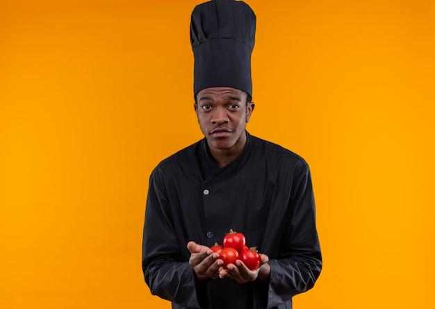 Młody pewny siebie afro-amerykański kucharz w mundurze szefa kuchni trzyma pomidory na rękach odizolowane na pomarańczowym tle z miejsca na kopię