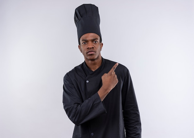Młody pewny siebie afro-amerykański kucharz w mundurze szefa kuchni wskazuje na bok na białym tle na białym tle z miejsca na kopię