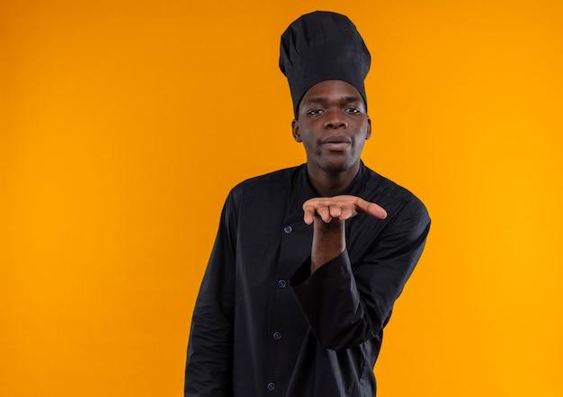 Młody pewny siebie afroamerykański kucharz w mundurze szefa kuchni wysyła pocałunek ręką odizolowaną na pomarańczowym tle z miejsca na kopię