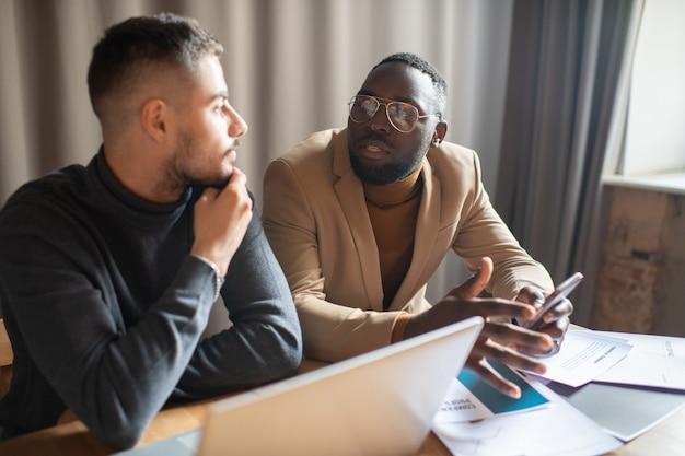 Młody pewny siebie biznesmen wyjaśniający punkt pracy męskiemu koledze