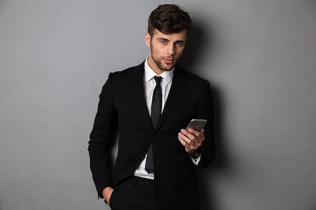Młody pewny siebie biznesmen z ręką w kieszeni trzyma telefon komórkowy,