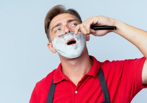 Młody pewny siebie blond męski fryzjer w mundurze rozmazanej twarzy z pianką do golenia brzytwa do golenia patrząc z boku na białym tle na białej przestrzeni z miejscem na kopię