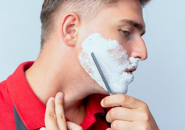 Młody pewny siebie blond męski fryzjer w mundurze rozmazanej twarzy z pianką do golenia z prostą brzytwą odizolowaną na białej przestrzeni z miejscem na kopię