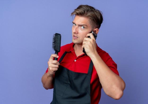 Młody pewny siebie blond męski fryzjer w mundurze trzyma grzebień i kładzie maszynkę do strzyżenia włosów na uchu na białym tle na fioletowej przestrzeni z miejsca na kopię