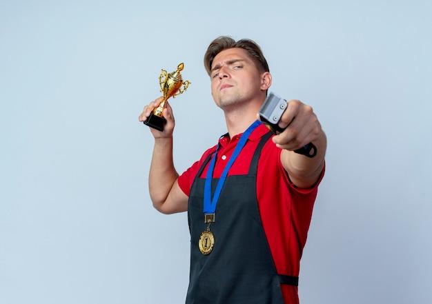 Młody pewny siebie blond męski fryzjer w mundurze ze złotym medalem trzyma puchar zwycięzcy i maszynkę do strzyżenia włosów na białym tle na białej przestrzeni z miejsca na kopię