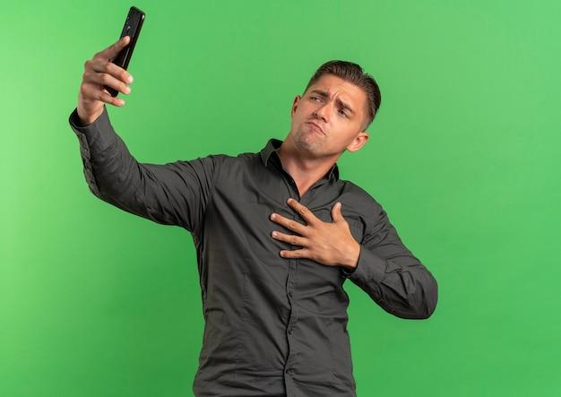 Młody pewny siebie blondynka przystojny mężczyzna kładzie rękę na klatce piersiowej patrzy na telefon, biorąc selfie na białym tle na zielonej przestrzeni z miejsca na kopię