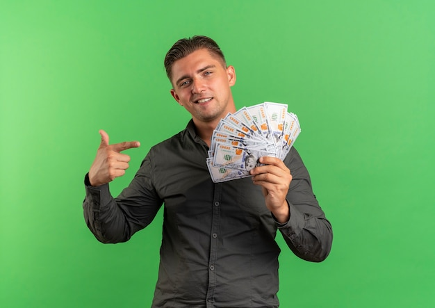 Młody pewny siebie blondynka przystojny mężczyzna trzyma i wskazuje na pieniądze na białym tle na zielonym tle z miejsca na kopię
