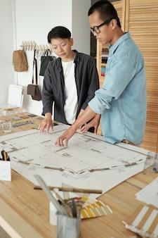Młody pewny siebie inżynier pokazujący koledze szkic budowy