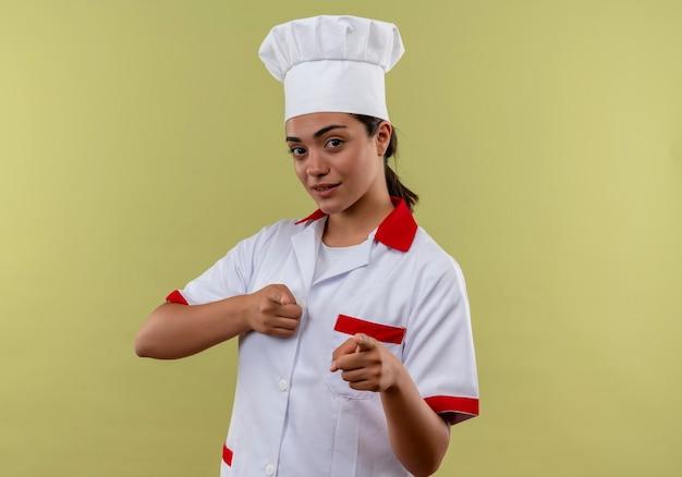 Młody pewny siebie kaukaski kucharz dziewczyna w mundurze szefa kuchni z dwoma palcami odizolowanymi na zielonej ścianie z miejsca na kopię