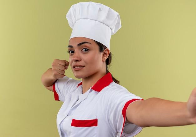 Młody, pewny siebie kaukaski kucharz w mundurze szefa kuchni trzyma pięść w górze i udaje, że trzyma na białym tle na zielonej ścianie z miejsca na kopię