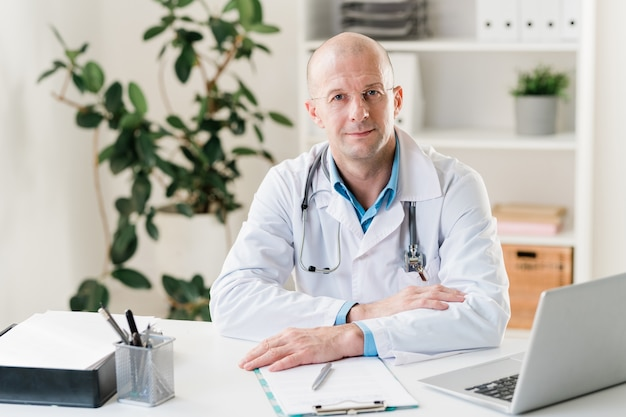 Młody, pewny siebie klinicysta w białym fartuchu siedzi przy biurku i przegląda dane online dotyczące swoich pacjentów