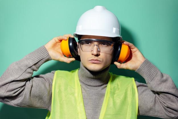 Młody, pewny siebie konstruktor, inżynier, założył słuchawki ochronne na uszy, nosił kask, gogle i kurtkę odblaskową na ścianie w kolorze aqua menthe.