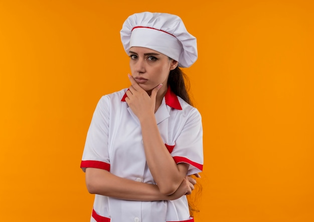 Młody pewny siebie kucharz kaukaski dziewczyna w mundurze szefa kuchni kładzie rękę na brodzie na białym tle na pomarańczowej ścianie z miejsca na kopię