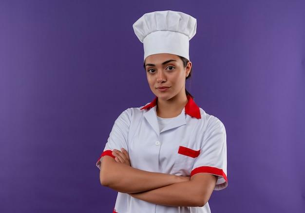 Młody pewny siebie kucharz kaukaski dziewczyna w mundurze szefa kuchni krzyżuje ramiona i patrzy na aparat odizolowany na fioletowej ścianie z miejsca na kopię