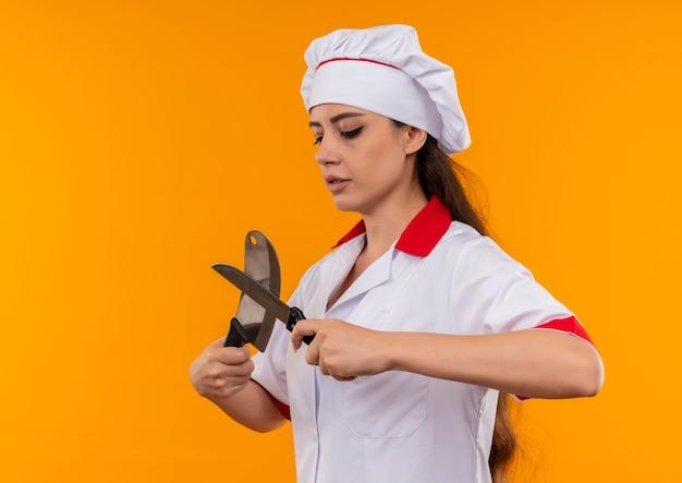Młody pewny siebie kucharz kaukaski dziewczyna w mundurze szefa kuchni przecina i patrzy na noże na białym tle na pomarańczowym tle z miejsca na kopię