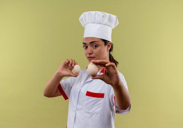 Młody pewny siebie kucharz kaukaski dziewczyna w mundurze szefa kuchni stoi bokiem i trzyma jajka na zielonej ścianie z miejscem na kopię
