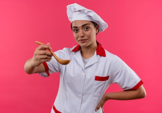 Młody pewny siebie kucharz kaukaski dziewczyna w mundurze szefa kuchni trzyma drewnianą łyżkę i kładzie rękę na talii odizolowaną na różowej ścianie z miejsca na kopię