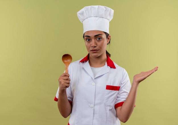 Młody pewny siebie kucharz kaukaski dziewczyna w mundurze szefa kuchni trzyma drewnianą łyżkę i trzyma rękę otwartą na białym tle na zielonej ścianie z miejsca na kopię