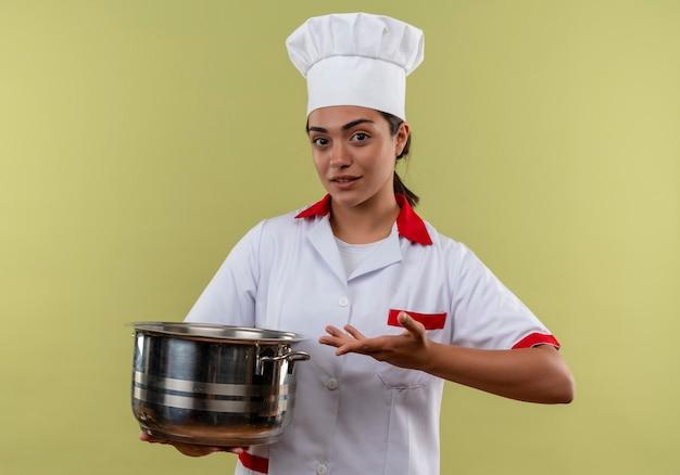 Młody pewny siebie kucharz kaukaski dziewczyna w mundurze szefa kuchni trzyma garnek i wskazuje ręką na zielonej ścianie z miejsca na kopię