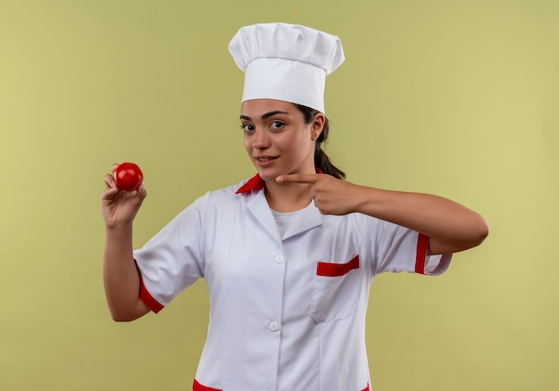 Młody pewny siebie kucharz kaukaski dziewczyna w mundurze szefa kuchni trzyma i wskazuje na pomidora na zielonej ścianie z miejsca na kopię