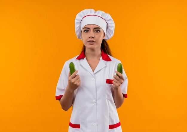 Młody pewny siebie kucharz kaukaski dziewczyna w mundurze szefa kuchni trzyma ogórki w obu rękach na pomarańczowej ścianie z miejsca na kopię