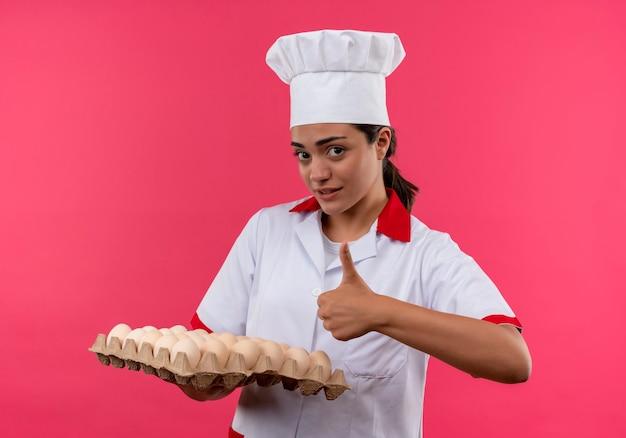 Młody pewny siebie kucharz kaukaski dziewczyna w mundurze szefa kuchni trzyma partię jaj i kciuki do góry na białym tle na różowej ścianie z miejsca na kopię