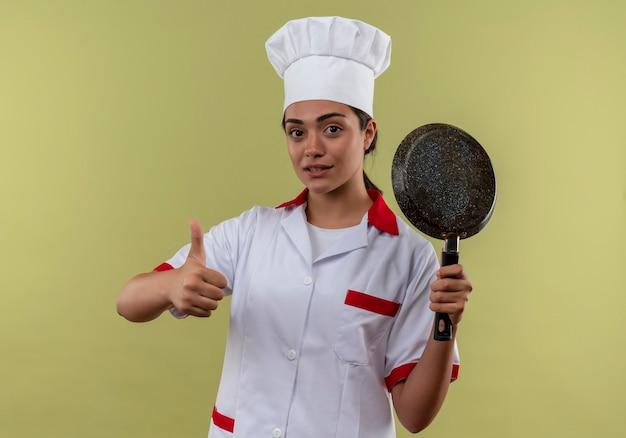 Młody pewny siebie kucharz kaukaski dziewczyna w mundurze szefa kuchni trzyma patelnię i kciuki do góry na białym tle na zielonej ścianie z miejsca na kopię