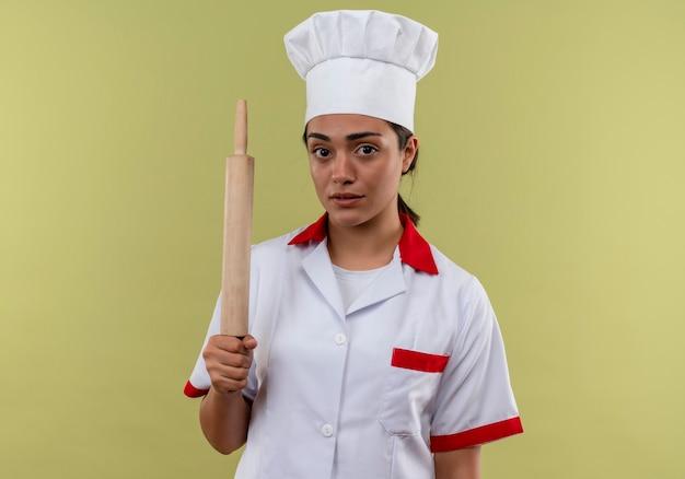 Młody pewny siebie kucharz kaukaski dziewczyna w mundurze szefa kuchni trzyma wałek do ciasta na białym tle na zielonej ścianie z miejsca na kopię