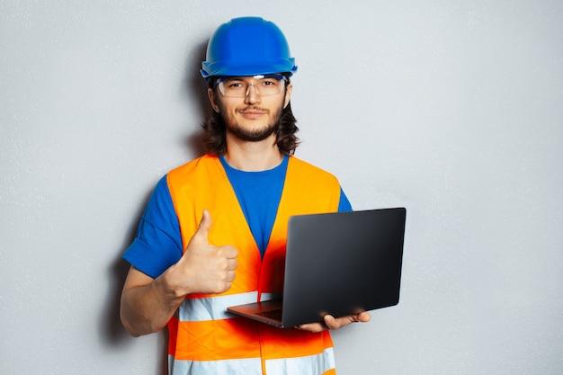 Młody pewny siebie mężczyzna, inżynier pracownik budowlany, ubrany w sprzęt bezpieczeństwa, trzymający laptopa i pokazujący kciuk na tle szarej ściany z teksturą.