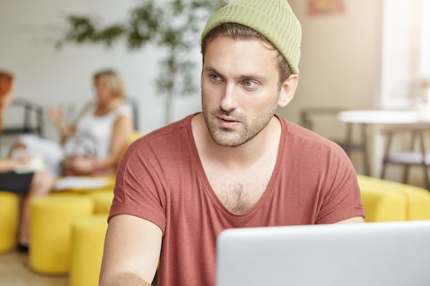Młody pewny siebie mężczyzna siedzi w kawiarni i pracuje na laptopie, spogląda zamyślony na bok, próbuje użyć wyobraźni