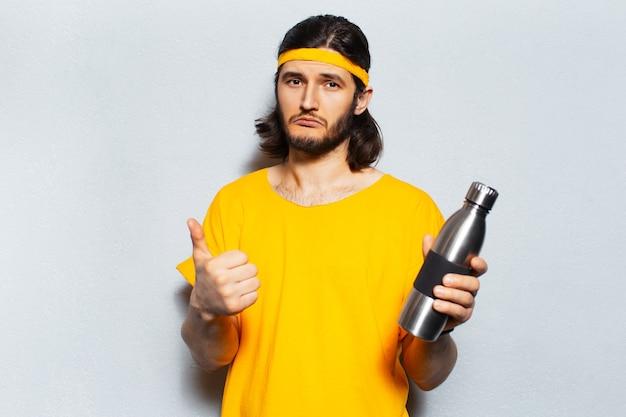 Młody pewny siebie mężczyzna trzyma termofor ze stali nierdzewnej, pokazując kciuk na tle szarej ściany z teksturą. zero marnowania. koncepcja butelek wielokrotnego użytku.