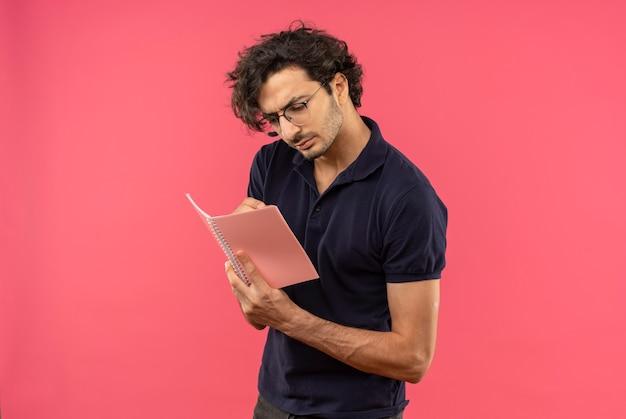 Młody pewny siebie mężczyzna w czarnej koszuli z okularami optycznymi trzyma i patrzy na notebook na białym tle na różowej ścianie