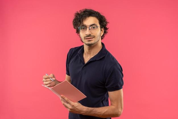 Młody pewny siebie mężczyzna w czarnej koszuli z okularami optycznymi trzyma notatnik i długopis patrząc na białym tle na różowej ścianie