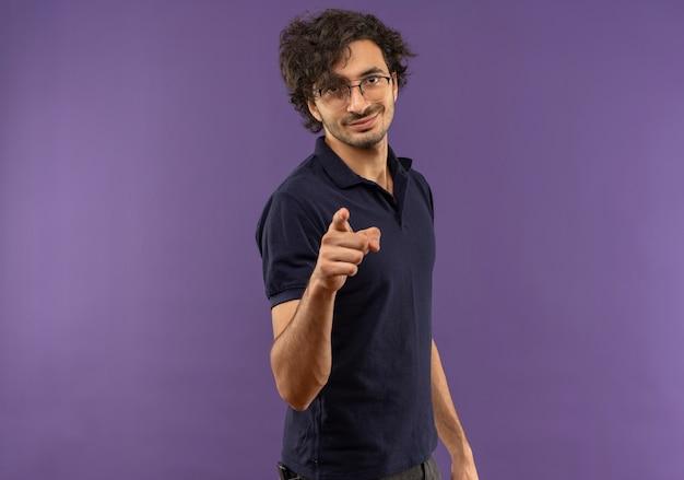 Młody pewny siebie mężczyzna w czarnej koszuli z punktami okularów optycznych na białym tle na fioletowej ścianie