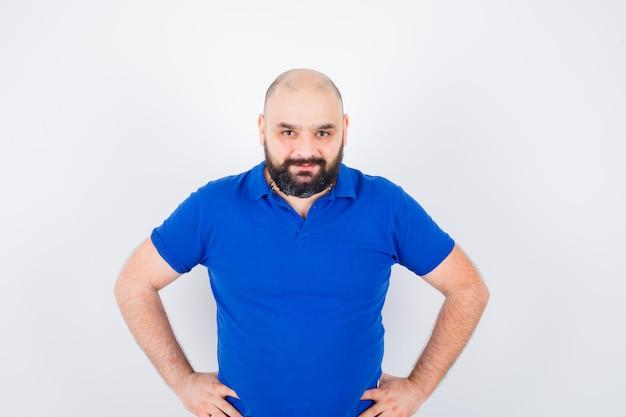 Młody pewny siebie mężczyzna w niebieskiej koszulce
