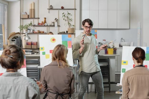Młody, pewny siebie nauczyciel kursu malarstwa, stojąc przed publicznością podczas lekcji i wyjaśniając coś uczniowi