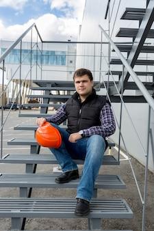 Młody pewny siebie pracownik w kasku siedzącym na metalowych schodach