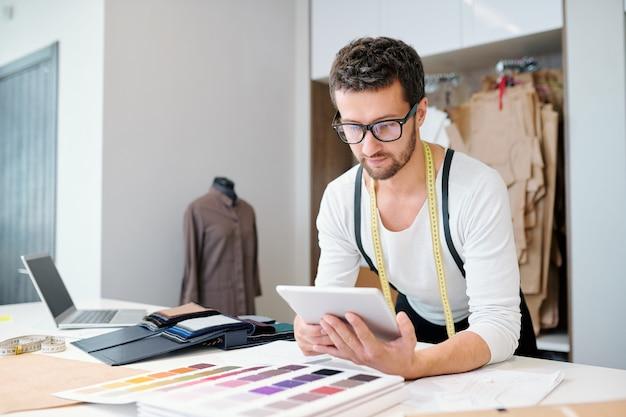 Młody, pewny siebie projektant mody z tabletem przewijającym pomysły i strony internetowe podczas pracy