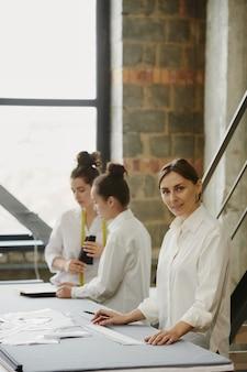 Młody pewny siebie projektant ubrań patrzy na ciebie, stojąc przy stole na ścianie dwóch kolegów omawiających nowe szkice