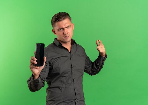 Młody pewny siebie przystojny blondyn trzyma telefon i wskazuje do przodu