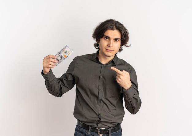 Młody pewny siebie przystojny kaukaski mężczyzna trzyma i wskazuje na pieniądze na białym tle na białym tle z miejsca na kopię