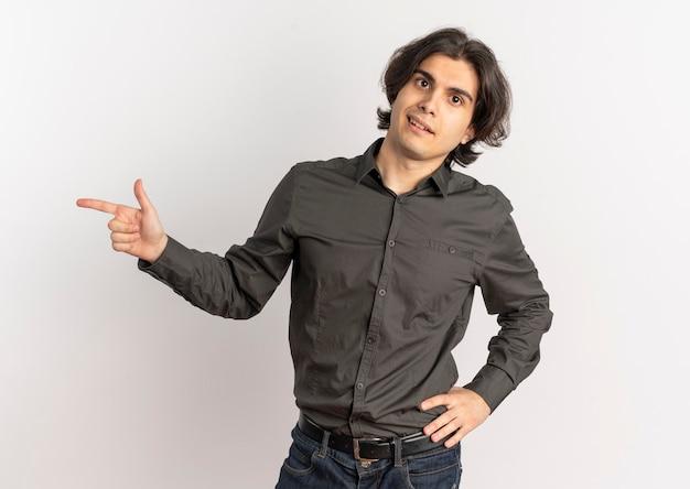 Młody pewny siebie przystojny kaukaski mężczyzna wskazuje na bok i kładzie rękę na talii na białym tle na białym tle z miejsca na kopię