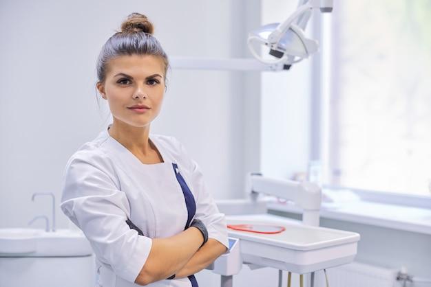 Młody pewny żeński lekarz dentysta z założonymi rękami