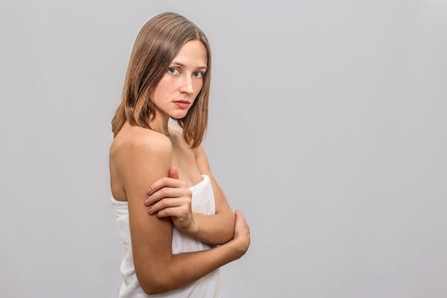 Młody piegowaty model stoi i pozuje. trzyma ręce skrzyżowane. młoda kobieta jest poważna i skoncentrowana. ma biały ręcznik na całym ciele.